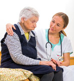 Elderly woman and young doctor stock photos