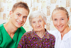 Elderly woman with the young doctors Royalty Free Stock Images