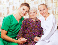 Elderly woman with the young doctors Stock Image