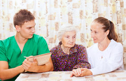 Elderly woman with the young doctors Royalty Free Stock Photo