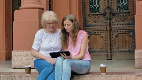 Elderly woman and young girl sits on the steps and using smartphone and drinking coffee. Vintage building in the background. stock video