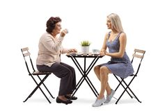 Elderly woman and young woman sitting at a table and drinking coffee stock photos