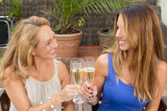 Elderly woman with a younger woman toasting with a glass of champagne Royalty Free Stock Photography