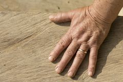 Elderly womans hand, a detail of an old woman hand on direct sun. Elderly womans hand with golden ring, a detail of an old woman hand on direct sunlight stock photography