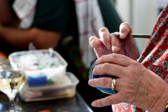 Elderly Womans Hands Crafting. Elderly woman's hands using a scapel to craft with modelling clay Royalty Free Stock Images