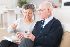 Elderly woman administering medication to husband from pillbox. Elderly women administering medication to husband from pillbox elderly stock photography