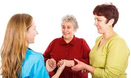 Elderly woman with carer and the young doctor. Elderly women with carer visit the young female doctor Stock Photos