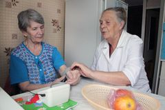 Elderly woman comforts her friend Stock Images