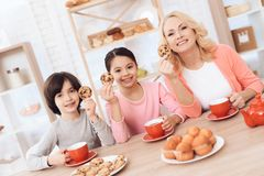 Elderly woman and cheerful grandson and granddaughter drink tea from red mugs in kitchen. royalty free stock photos