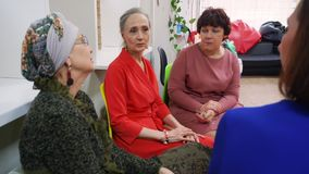 Elderly women discuss their problems in the psychological support group. Senior women at the meeting with psychologist. They discuss their problems in the stock video footage