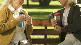 Elderly women drinking tea from thermos flask, water balance in body, hydration. Stock footage stock footage