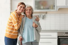 Elderly woman with female caregiver in kitchen. Elderly women with female caregiver in kitchen. Space for text stock photo