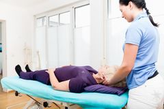 Senior woman visiting physiotherapist for massage Royalty Free Stock Images