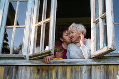Elderly woman and her adult daughter from the window of house. Elderly women and her adult daughter from the window of village house royalty free stock images