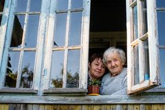 Elderly woman and her adult daughter in window of village house. Family. Elderly women and her adult daughter in window of village house royalty free stock photos
