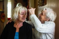 Elderly woman talking to her adult daughter. royalty free stock image
