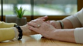Elderly women holding hands. Two people at the table. How to be supportive stock video footage