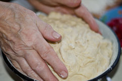 Elderly women kneads dough. The hands of an elderly women knead the dough Royalty Free Stock Photography