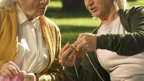 Elderly women knitting outdoor, hobbies for seniors, diy and creativity, closeup. Stock footage stock video