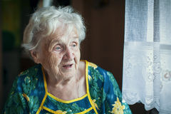 Elderly women looking out the window. Stock Photos