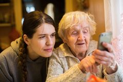 Elderly woman looks and typing on a smartphone, with his adult girl granddaughter. Family. royalty free stock photos