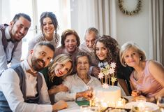 An elderly woman with multigeneration family celebrating birthday on indoor party. An elderly women with multigeneration family and a cake celebrating birthday stock photos