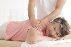 Masseur setting elderly woman shoulder. Elderly women with pain lying on massage bed and masseur setting her shoulder stock photos