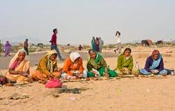 Elderly women prepare prasadam to a religious ceremony in a desert Stock Photography