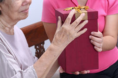 Elderly woman receiving a gift from daughter. Elderly women receiving a gift from daughter , mathers day royalty free stock images