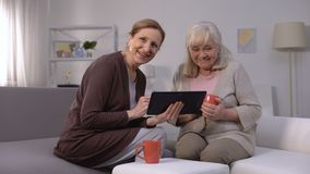 Elderly women smiling, watching entertainment show on tablet, fast internet. Stock footage stock video