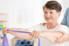 Elderly woman pulling elastic band. Elderly women standing with her arms forward and pulling an elastic band in physiotherapy stock photo