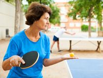 Elderly woman starts a party in table tennis. Elderly women starts a party in table tennis at outdoor royalty free stock image