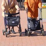 Elderly women together street walker rollator shopping. Two elderly women are shopping and walking together with walker rollators in the street outdoors. Aging royalty free stock image