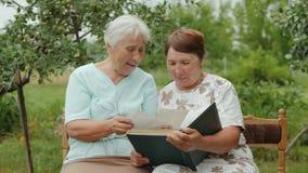 Elderly women view photos in an album outdoors