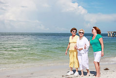 Elderly women walking beach. Three senior women friends walking at the beach royalty free stock images