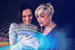 An elderly woman and a young girl listen to music together. Communication between people of different generations. An elderly women and a young girl listen to Stock Image