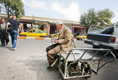 Elderly worker counts the money earned for a rough day. SANANDAJ, IRAN: Elderly worker counts the money earned for a rough day. With a population of 380.000 Royalty Free Stock Photo