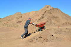 The elderly worker is lucky a wheelbarrow with soil on road cons Royalty Free Stock Photography