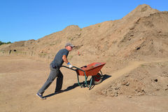 The elderly worker is lucky a wheelbarrow with soil on road cons Royalty Free Stock Images
