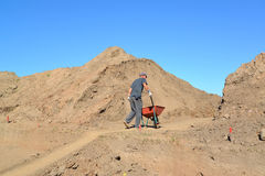 The elderly worker is lucky a wheelbarrow with soil on road cons. Truction Stock Images