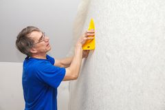 Elderly worker smoothing wallpaper Royalty Free Stock Photos