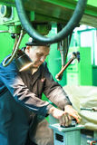 Elderly worker watches on milling machine work Royalty Free Stock Photography