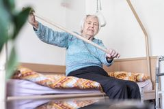 Elderly 96 years old woman exercising with a stick sitting on her bad. royalty free stock photo