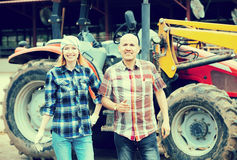 Elderly and young farmers working at machinery Royalty Free Stock Image