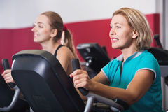 Elderly and young women working out in gym stock image