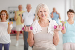 Elders with dumbbells. Active happy elders with colorful dumbbells during training Royalty Free Stock Photo