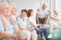 Elders holding water bottles. Happy elders sitting on exercise balls and holding water bottles Royalty Free Stock Photo