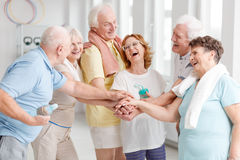 Elders laughing before yoga classes. Happy elders gathering hands and laughing before yoga classes royalty free stock photography