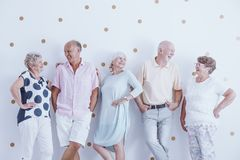 Elders looking at each other. Happy elders leaning against white wall with dots and looking at each other Stock Photo
