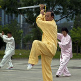 Elders Playing Taiji Sword. Elders prefer to play Taiji early in the moring, the prime time of a day for the players to take in the essence of the rising sun Royalty Free Stock Image